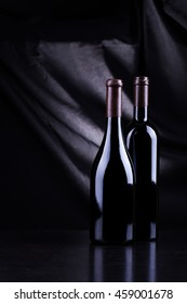 Two bottles of wine over a dark background