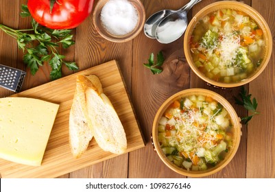 Two bowl of minestrone soup with cheese on cutting board, vegetables on rustic wooden background, top view, long width.