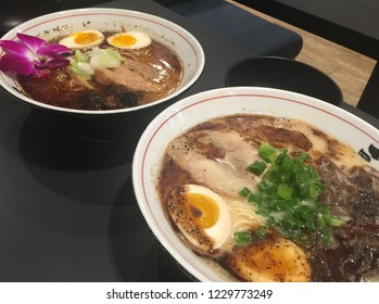 Two bowl of Miso and Black Tonkatsu Ramen with chasiu and soft boiled eggs toppings on black table/background.