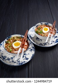 Two bowl of shin noodles, with medium-boiled egg, slices of chicken breast and green scallions