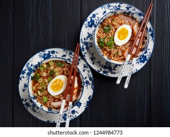Two bowl of shin noodles, with medium-boiled egg, slices of chicken breast and green scallions, flatlay