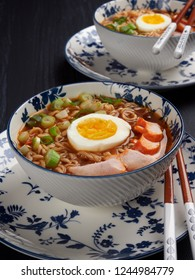 Two bowl of shin noodles, with mediun-boiled egg, slices of chicken breast and green scallions