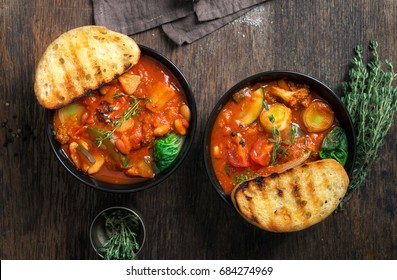 Two bowl of soup minestrone with seasonal vegetables on wooden table close up, top view. Italian food