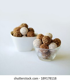 Two bowls of an assortment chocolate balls and rum balls.  This is against a isolated white background.