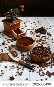 Two bowls with coffee beans and ground coffee, a coffee grinder, cinnamon sticks on a light wooden background. View from above. Vertical