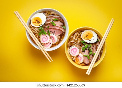 Deux bols de soupe japonaise à la soupe de nouilles avec bouillon de viande, porc tranché, narutomaki, oeuf au jaune sur fond jaune pastel. Plat traditionnel du Japon, vue de dessus, gros plan, concept