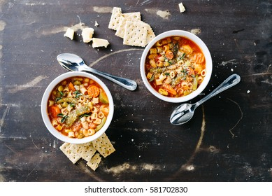 Two bowls of minestrone soup topped with fresh herbs and served with saltine crackers in white bowls on a rustic brown surface.
