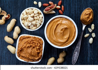 Two bowls of peanut butter and peanuts on dark wooden background from top view