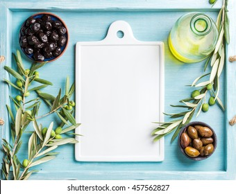 Two bowls with pickled green and black olives, olive tree sprigs and oil with white ceramic board in center. Blue Turquoise background, copy space, top view