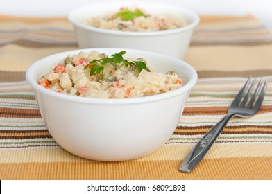 Two bowls of potato salad and a fork on decorative  yellow napkin