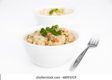 Two bowls of potato salad with a fork on white isolating background