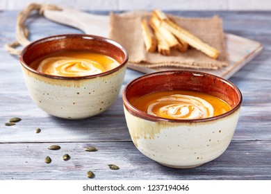 Two bowls of pumpkin soup on white and gray background.