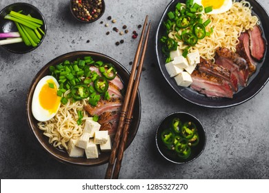 Two bowls of tasty Asian noodle soup ramen with meat broth, tofu, pork, egg with yolk on grey rustic concrete background, close up, top view. Hot tasty Japanese ramen soup for dinner asian style