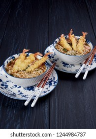 Two bowls of tempura udong noodles, with shrimps tempura, in white and blue bowls and chopsticks, on dark blue background