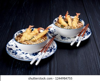 Two bowls of tempura udong noodles, with shrimps temputa, in beige bowls with red chopsticks, on dark blue background