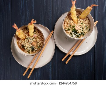 Two bowls of tempura udong noodles, with shrimps temputa, in beige bowls with wooden chopsticks, on dark blue background