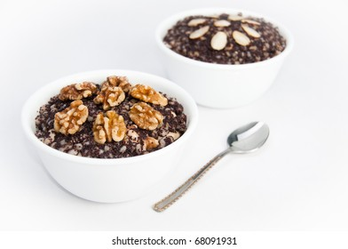 Two bowls of traditional sweet Kutia dessert with a spoon on white isolating background