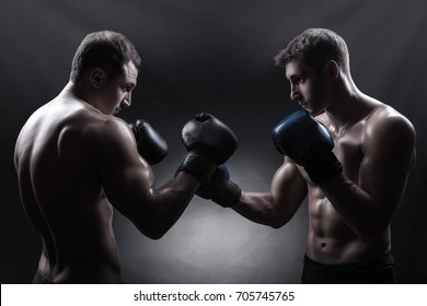 Two boxer with boxing gloves before a fight against a dark background