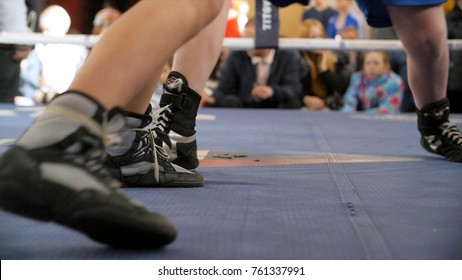 Two boxers fight in the boxing ring in boxing shoeses. Low section of male boxer standing against referee by athlete lying in boxing ring
