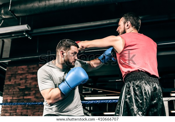 Two boxers train on the ring. Kicking and blocking the hit. One athlete in blue boxing gloves, the second in a red sports uniform. Athletes are fighting against a background of a brick wall loft.