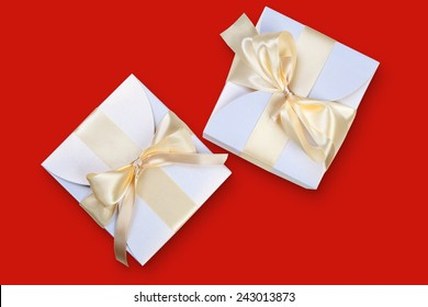 Two boxes with gold ribbon on red