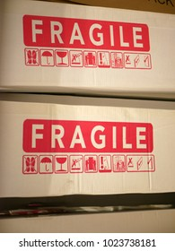 Two boxes with red writing and icons to warn about fragile contents, illustrate concept of emotional fragility