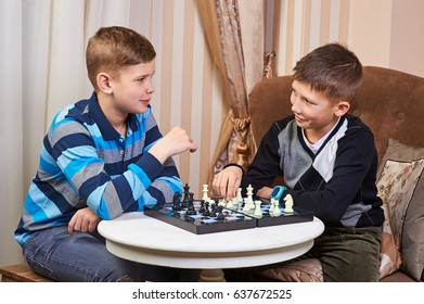 Two boy children playing chess at the table. the concept of childhood and board games, brain development and logic