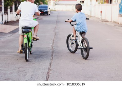 Two boy friends riding bicycle for relaxation.Happy time for children.