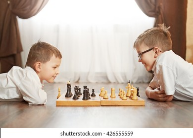 Two boy playing chess, studio, background
