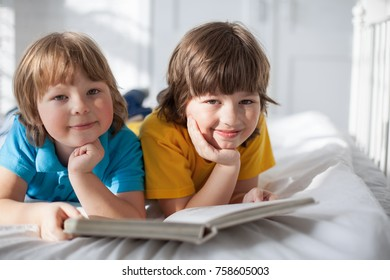 two boy read book indoors