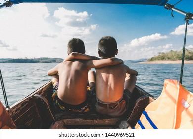 Two boy sit on the boat looking beautiful sky add noise picture. Dear friend