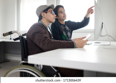 Two boy sitting and using computer
