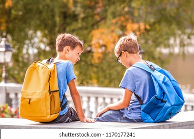 Two boys after school, sitting on bench and talking