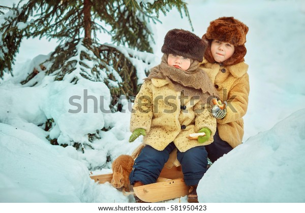 Two boys brother enjoy a sleigh ride. Child sledding. Toddler kid riding a sledge. Children play outdoors in snow. Kids sled in winter.  Little rabbits in the hands.