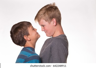 Two Boys (brothers) in profile having a staring contest.