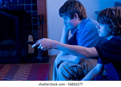 Two boys (brothers) watching TV, bored and channel surfing