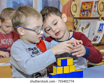 two boys are buildind a lego house in kindergarten