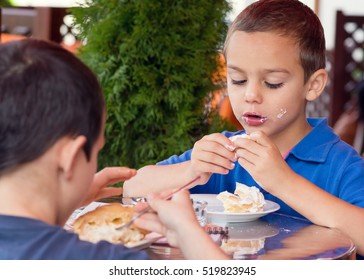 Two boys children eating and enjoying cake in a cafe.