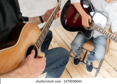 Two boys of different ages sitting with guitar in hands and playing it