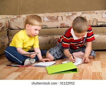 two boys draw with paints sitting on floor