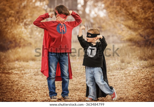 Two boys dressed as superheroes compare their power in the playground summer day