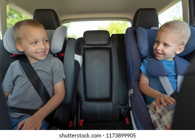 Two boys are driving in car seats. Safety of children while traveling by car