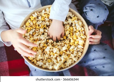 two boys eating popcorn on a sofa in the dining room