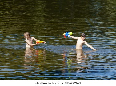 Two Boys Fighting with Squirt Guns in the Lake.