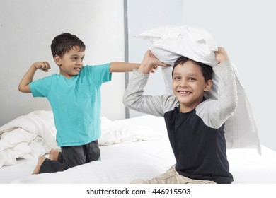 Two boys are fighting their bed room with white pillow