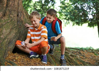 Two Boys Finding Item Whilst Geocaching In Forest