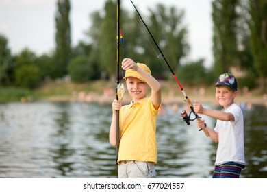 Two boys are fishing on the beach at sunset