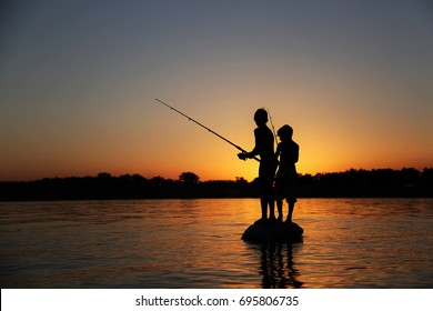 Two boys are fishing, silhouette.