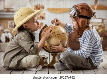 Two boys in the form of pilot and tourists planning on a globe of their travel route