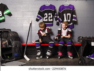Two Boys Get Dressed in hockey gear in dressing room before game